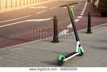 Electric Scooter Parked On The Road. Modern Eco Electric City Scooters For Rent Outdoors On The Side