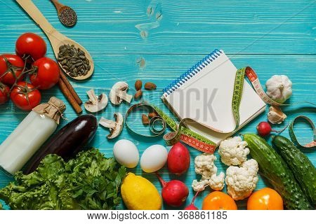 A Set Of Products For An Alkaline Diet, A Notepad And A Centimeter On A Wooden Aquamarine Background