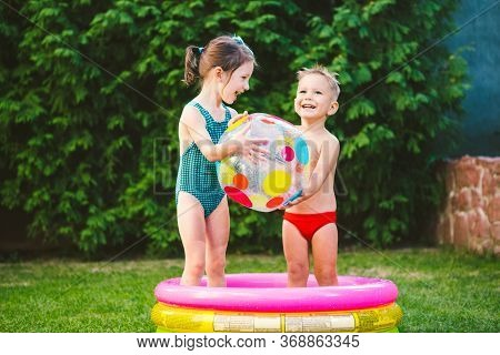 Two Children With Beach Ball At Swimming Pool. Joyful Kid Playing In Inflatable Pool Backyard. Littl