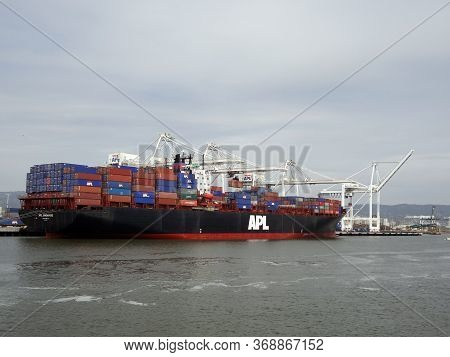 Oakland - April 21, 2011: Apl Shipping Line Shipping Boat Is Unloaded By Cranes In Oakland Harbor On