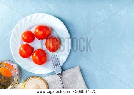 Juicy Spicy Marinated Tomatoes On A White Plate On Blue Surface. Top View With Copy Space.
