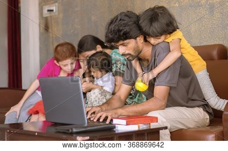 Children Or Kid Playing By Riding On Father Back And Disturbing While Father Busy In Working On Lapt