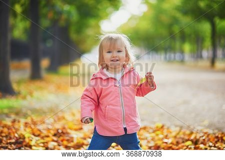 Adorable Cheerful Toddler Girl Running In Tuileries Garden In Paris, France. Happy Child Enjoying Wa