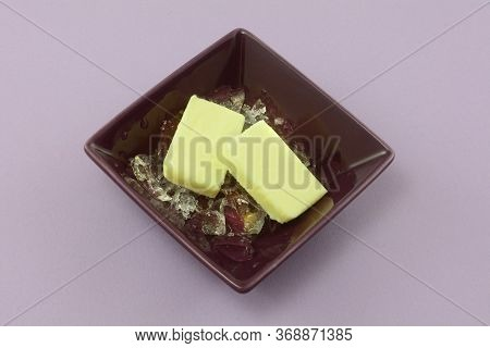 Two Pats Of Butter On Ice To Prevent From Melting In Warm Temperatures In Purple Butter Dish On Lave