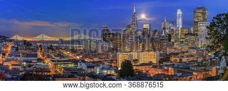 San Francisco City Skyline Panorama At Sunset With Downtown Skyline, Bay Bridge And Full Moon Betwee