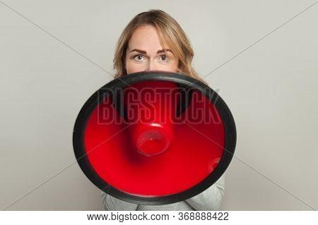 Woman With Big Loudspeaker Megaphone. Girl Holding Red Bullhorn