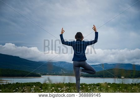 A Young Woman Doing Yoga In The Field.