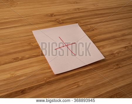 A Paper Sticker Pasted On A Wooden Surface With The Image Of The Plus Symbol
