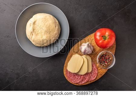 Ingredients For Cooking Homemade Pizza With Mozzarella And Salami On A Dark Background. Top View. Co