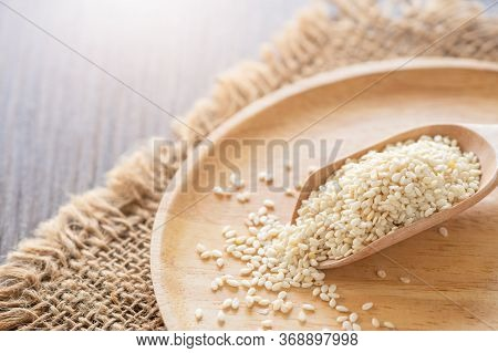 White Sesame Seeds In A Wooden Spoon On Wood Table. White Sesame Is Rich In Calcium And Phosphorus.