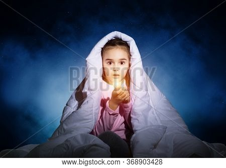 Frightened Girl With Flashlight Hiding Under Blanket. Scared Kid Lying In His Bed At Home. Night Ter