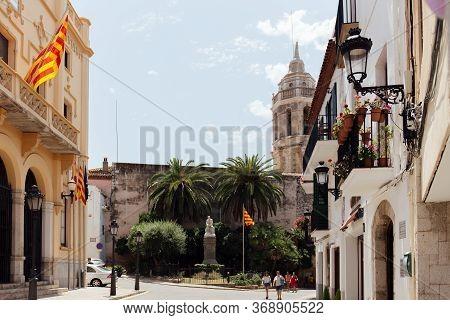 Barcelona, Spain - April 30, 2020: La Senyera Flags On Buildings On Urban Street With Church Of San