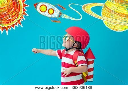 Happy Child Playing With Toy Paper Jet Pack Against Blue Background. Kid Having Fun At Home. Imagina
