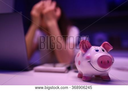 Piggy Bank On Table, An Upset Woman Sits Behind. Global Economic Processes Affect The Family. Revisi