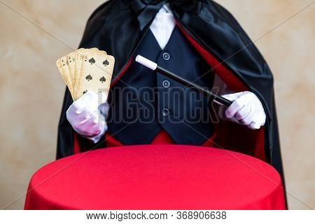 Illusionist Holding Magic Wand And Playing Card. Imagination And Magic Concept
