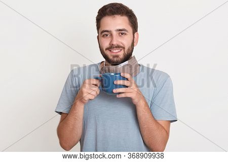 Indoor Photo Of Cheerful Sincere Young Man Having Beard, Looking Directly At Camera, Holding Cup Wit