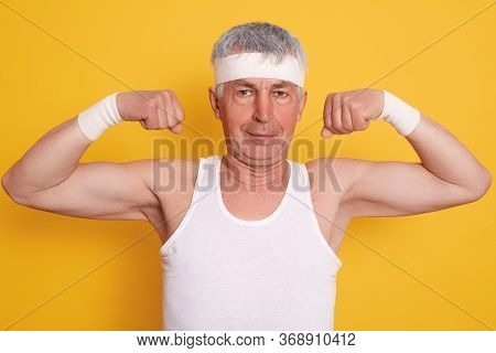 Elderly Man Dresses White Headband Showing His Biceps And Power, Looks At Camera, Posing Against Yel