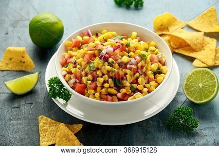Mexican Corn Salsa In White Bowl With Lime And Tortilla Chips. Healthy Food