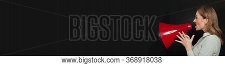 Girl Holding Big Red Bullhorn On Black Banner Background With Copy Space. Woman Screaming With Louds