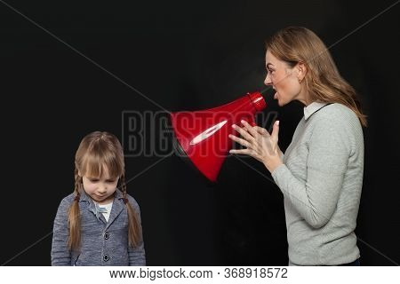 Woman Shouting In Loudspeaker To Sad Child Girl On Black Background. Abuse Concept