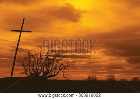 Crucifix And Leafless Tree On Horizon With Orange Cloudy Sky On The Way Of St. James. A Famous Pilgr