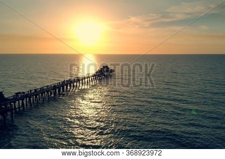 Silhouette Of A Pier Over The Water At Sunset. Naples Beach And Fishing Pier At Sunset, Florida. Sma