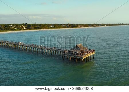 Naples Beach And Fishing Pier At Sunset, Florida. Sunset Over The Gulf Of Mexico, Drone Flying Above