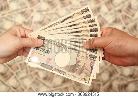 Yen - Japanese Money: Hands Holding (paying / Receiving) 100,000 Yen Banknote. Isolated On Blurred B