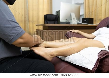 Quarantine asian woman do foot massage at home while city lockdown for social distance due to coronavirus pandemic. Massage and spa is one of service business that shutdown while city lockdown.