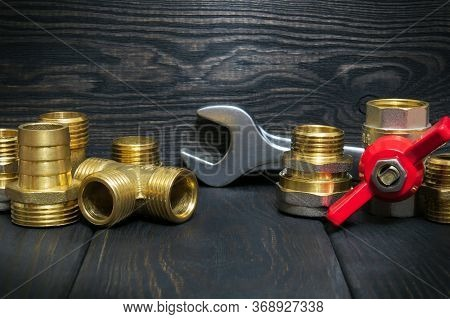 Brass Fittings And Tool On Vintage Dark Boards Used In Plumbing Or Gas Piping