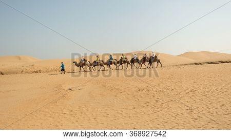 Kubuqi Desert, Inner Mongolia Province / China - July 31, 2016: Guide Taking Tourists On Two-humped