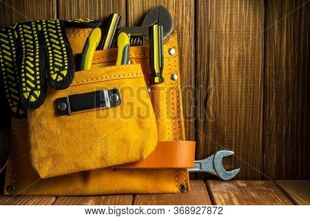 Tools And Instruments In Leather Bag On Vintage Wooden Boards
