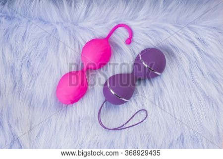 Collection Of Different Types Pink And Violet Vaginal Balls , Sex Toys On Violet Background.