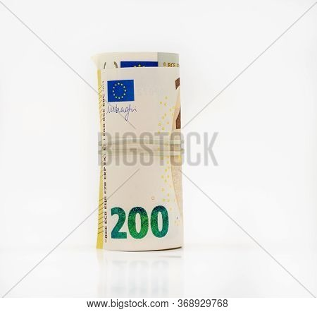 Banknotes Two Hundred 200 Euros In A Roll With An Elastic Band. European To Save. Close-up, White Ba