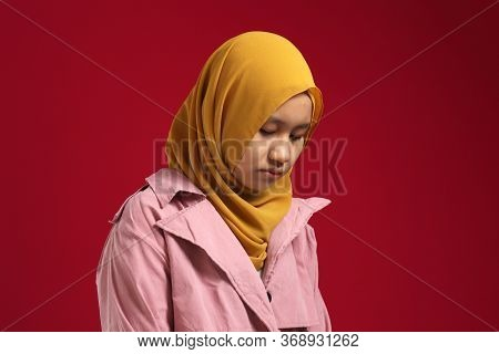 Portrait Of Sad Young Asian Teenage Muslim Girl Wearing Hijab Looking Down And Depressed, Standing A