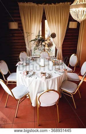 Wedding Table Setting With Empty Wine Glasses And Fresh Flowers