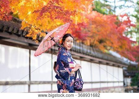 Geishas Girl Wearing Japanese Kimono Among Red Wooden Tori Gate At Fushimi Inari Shrine In Kyoto, Ki