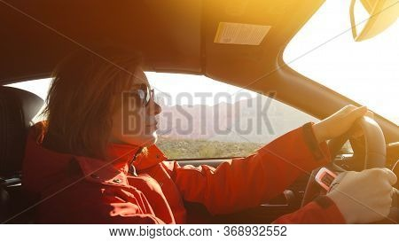 Woman Driving A Car. Young Woman Is Driving A Car On A Sunny Day. Confident Woman In Sunglasses Driv