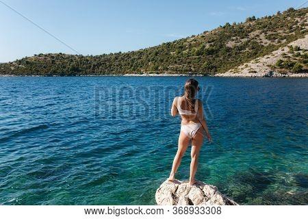 Sexy Woman In Bikini Stand On The Rock By The Sea. Beautiful Lagoon. Woman Enjoying Summer Sun. Back