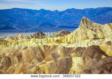 Zabriskie Point is part of the Amargosa Range. Death Valley in California, USA. Magnificent erosion landscape of various shades. Sunset. The concept of active, extreme and photo tourism