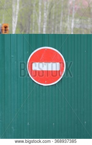 Red Round Road Sign With White Stripe Prohibiting Movement On The Green Fence Of Sheet Iron. Do Not