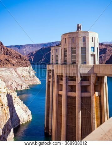 Hoover Boulder Dam is a unique hydraulic structure in the USA, concrete arch-gravity dam and hydroelectric power station. Sunset. The concept of cognitive, active and photo tourism
