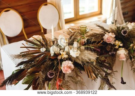 The Presidium With Floral Arrangement With Pampass Grass And Candles Of The Newlyweds At The Wedding