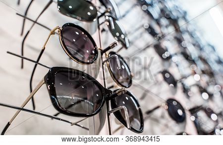 Sunglasses In The Shop Display Shelves. Stand With Glasses In The Store Of Optics. Sales Rack Of Sun