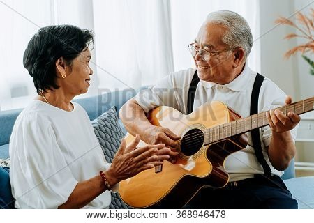 Asian Senior Couple Sitting On The Sofa And Playing Acoustic Guitar Together. Happy Smiling Elderly