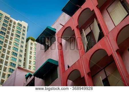 Old Red Pink Building Behind There Is A Large And Tall Modern Condominium On A Bright Blue Sky Day.