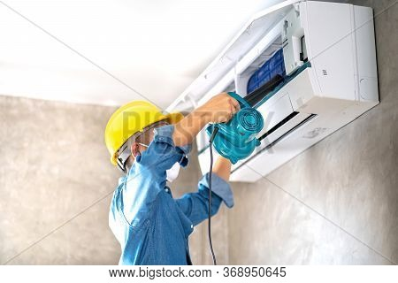Technician Man Repairing ,cleaning And Maintenance Air Conditioner On The Wall With Blower In Bedroo