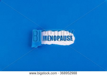 The Text Menopause Appearing Behind Torn Blue Paper.