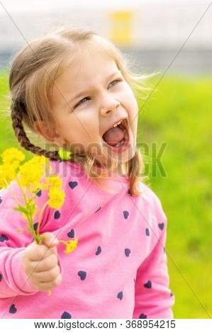 Little Girl With Yellow Flowers On A Sunny Day, Backlight