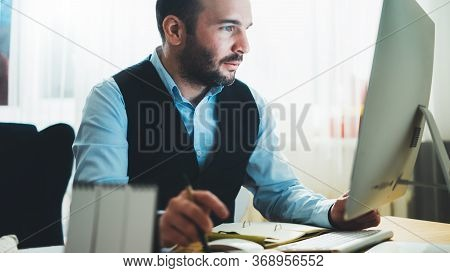 Man Thinking Looking In Monitor Computer At Home Workplace. Social Distance Bearded Businessman Work